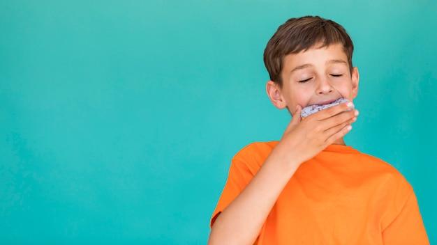 Rapaz comendo uma rosquinha com espaço para texto