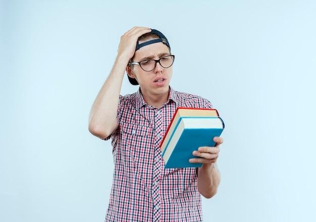 Rapaz confuso, jovem estudante usando óculos e boné, segurando e olhando para livros