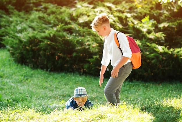 Rapaz dá a mão ao irmão mais novo para passear. o menino da escola ajuda a levantar o amigo. as crianças ajudam e apoiam umas às outras. crianças caminhando juntos no parque de verão. irmãos felizes ao ar livre.