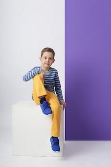 Rapaz da moda em roupas elegantes na parede colorida