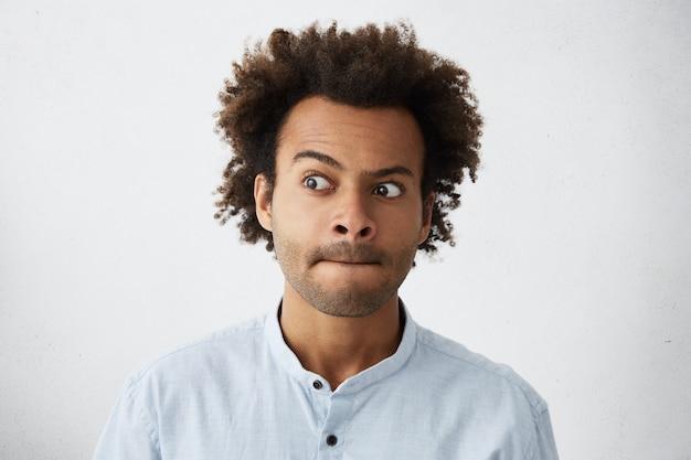 Rapaz de aparência agradável com penteado africano hesitando pressionando os lábios e olhando para o lado
