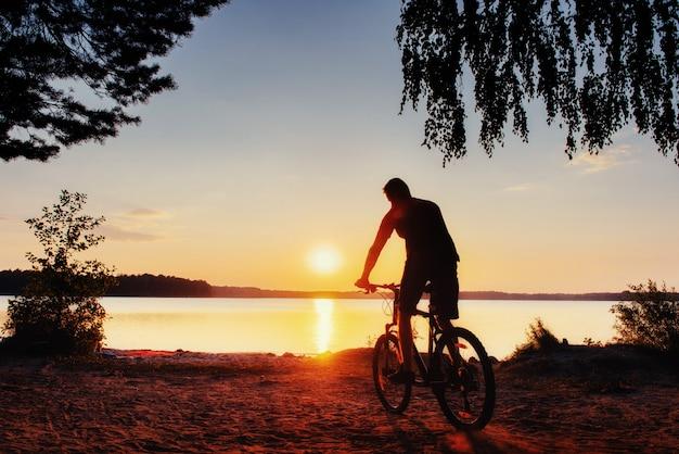 Rapaz de bicicleta ao pôr do sol. cárpatos, ucrânia, europa