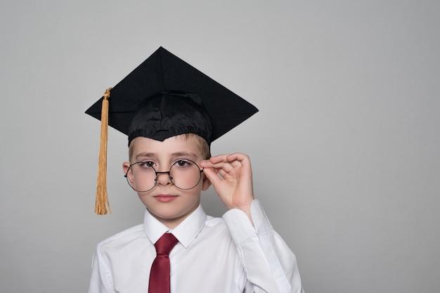 Rapaz de boné quadrado acadêmico e camisa branca, corrigindo os óculos