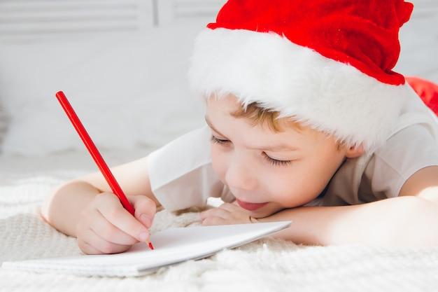 Rapaz de boné vermelho escreve uma carta para o papai noel