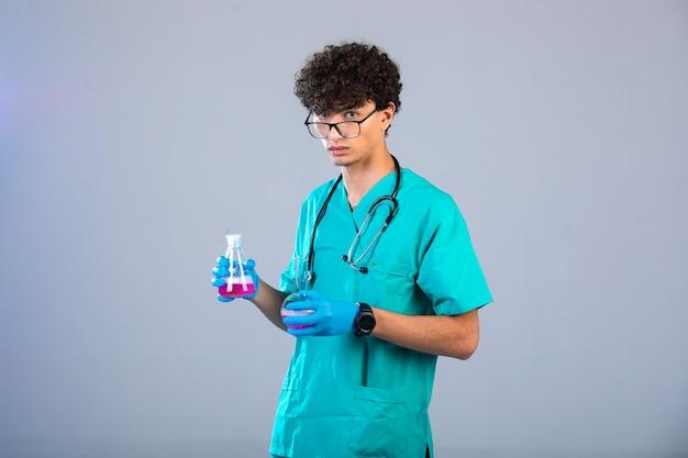 Rapaz de cabelo encaracolado com uniforme médico e máscaras de mão segurando frascos químicos no fundo cinza