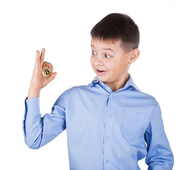 Rapaz de camisa azul olha com surpresa o bitcoin na mão