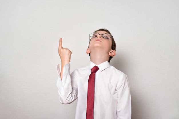 Rapaz de camisa branca e óculos aponta o dedo para cima. conceito de escola fundo branco.