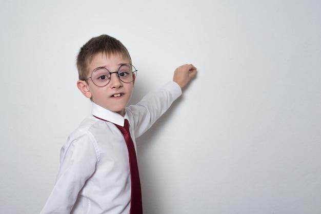 Rapaz de camisa, gravata e óculos escreve no quadro. estudante do ensino médio. copie o espaço