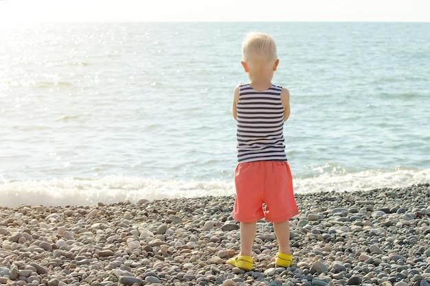 Rapaz de camiseta listrada está de pé na praia