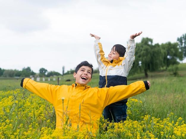 Rapaz de capa de chuva e seu irmão cercado por flores
