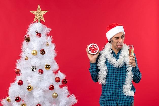 Rapaz de cara azeda com chapéu de papai noel e segurando uma taça de vinho e um relógio em pé perto da árvore de natal no vermelho