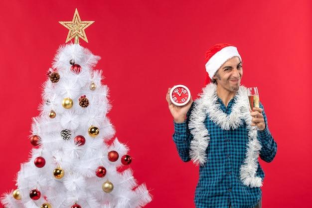 Rapaz de cara azeda com chapéu de papai noel, levantando uma taça de vinho e segurando o relógio perto da árvore de natal no vermelho