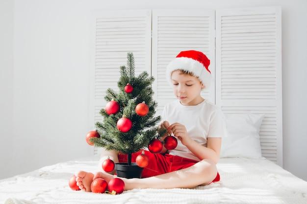Rapaz de chapéu de papai noel vermelho decora uma pequena árvore de natal
