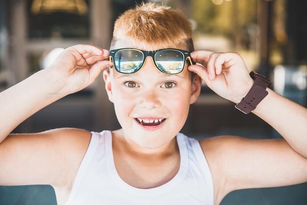 Rapaz de jeans e óculos de sol na cidade.