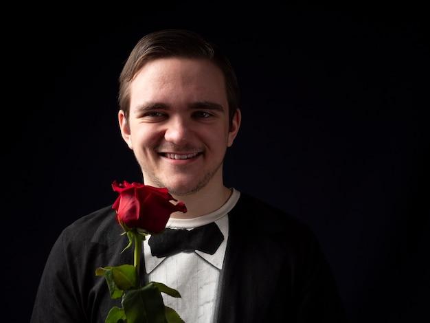 Rapaz de terno preto com uma rosa vermelha nas mãos e sorrindo no preto