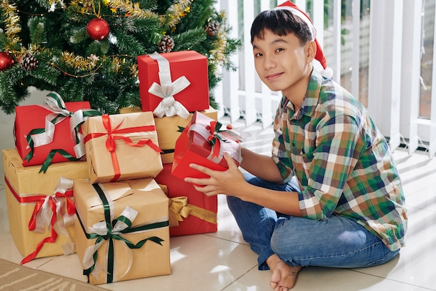 Rapaz, desfrutando de abrir os presentes de natal