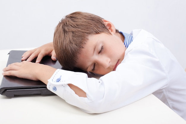 Rapaz dormindo enquanto estiver usando seu computador portátil