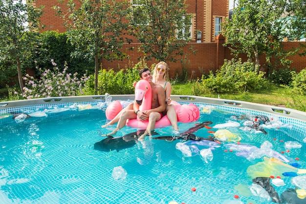 Rapaz e garota se divertindo enquanto o meio ambiente está poluído, conceito de problema de reciclagem de plástico e coleta de lixo.