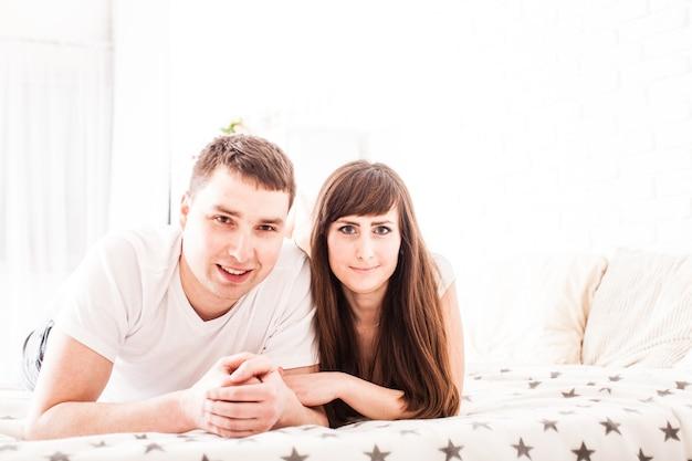 Rapaz e mulher estão deitados na cama e se divertem