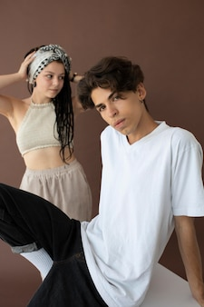 Rapaz e rapariga adolescente da moda a posar juntos