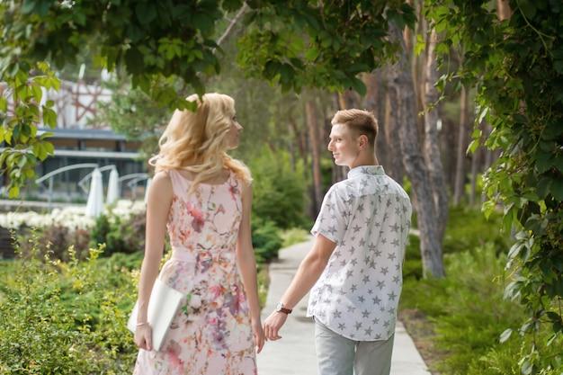 Rapaz e rapariga encontram-se num caminho estreito no jardim