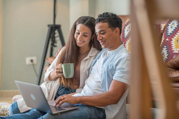 Rapaz e rapariga juntos em casa a desfrutar do computador portátil sentado no chão, a sorrir e a rir - nova vida, casados, pessoas apaixonadas e por relacionamento divertem-se a ver a web online