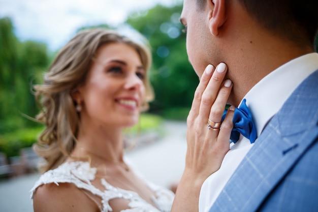 Rapaz elegante com a fantasia de noivo e noiva linda garota em um vestido branco com um passeio de trem no parque no dia do casamento