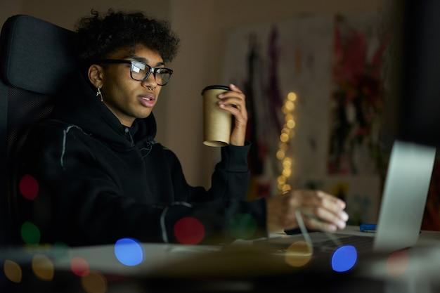 Rapaz elegante com piercing usando óculos, segurando uma xícara descartável de café sentado no