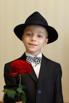 Rapaz elegante de terno e chapéu com uma rosa