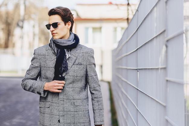 Rapaz elegante em óculos de sol no casaco com maleta na rua