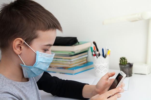 Rapaz em casa escolaridade com um smartphone nas mãos e uma máscara médica. conceito de quarentena de coronavírus