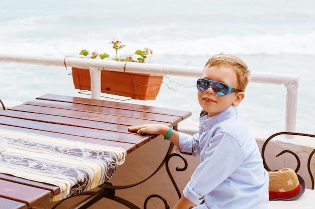 Rapaz em restaurante na praia do mar,