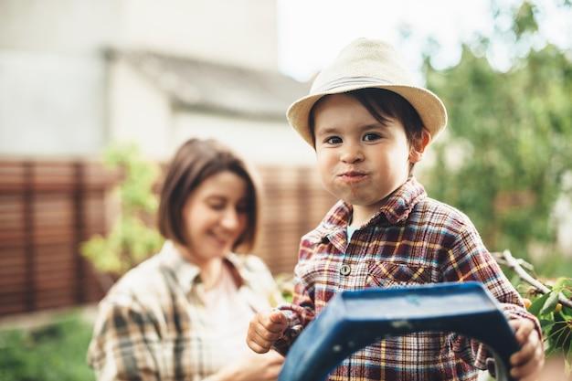 Rapaz encantador, caucasiano, com um chapéu na cabeça, comendo cerejas da árvore, posando com a mãe no fundo, sorrindo