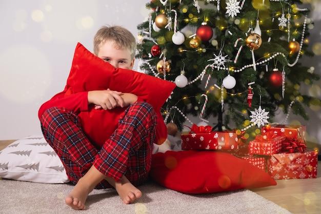 Rapaz engraçado com clima festivo de pijama de natal e travesseiro aconchegante sentado perto da árvore de natal com presentes