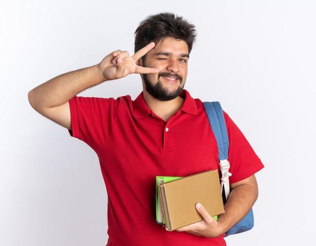 Rapaz engraçado jovem barbudo estudante em uma camisa pólo vermelha com mochila segurando cadernos olhando sorrindo e piscando mostrando o sinal v em pé