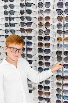 Rapaz, escolhendo óculos, olhando para a câmera em óptica
