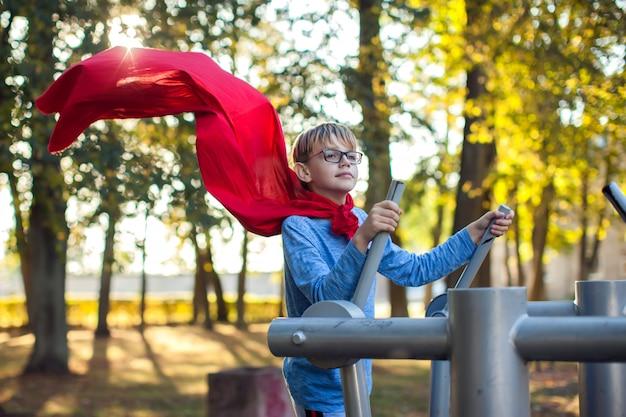Rapaz esperto com capa vermelha faz exercícios em equipamentos de treinamento ao ar livre e se sente como um herói