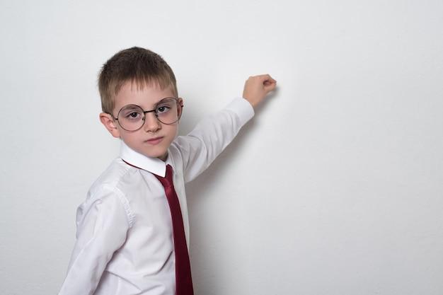 Rapaz esperto com óculos e uniforme escolar escrevendo a bordo. conceito de ensino médio. copie o espaço.