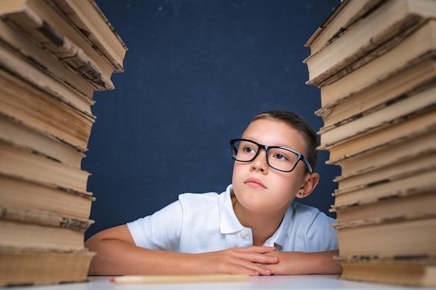 Rapaz esperto de óculos sentado entre duas pilhas de livros e desvia o olhar pensativo