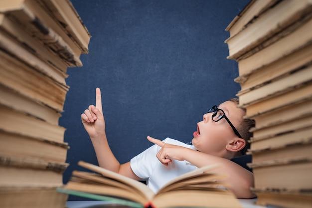 Rapaz esperto de óculos sentado entre duas pilhas de livros e olha para cima, apontando o dedo