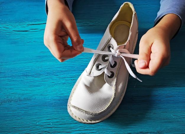 Rapaz está aprendendo a amarrar cadarços, close-up nas mãos e no sapato