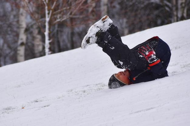 Rapaz está rolando montanha abaixo no inverno nas costas. criança cai de lâmina de neve.