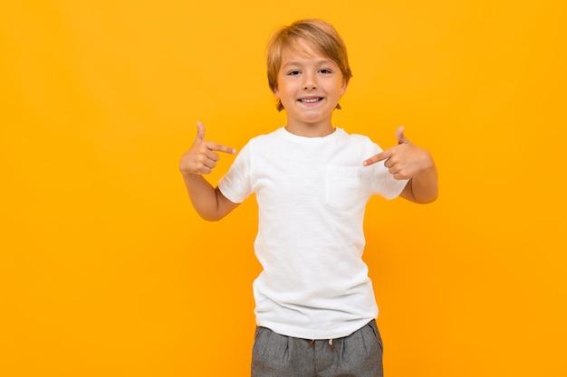Rapaz europeu atraente em uma camiseta branca em uma parede laranja com espaço de cópia