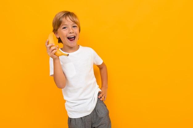 Rapaz europeu atraente em uma camiseta branca, falando em uma banana como no telefone em uma parede amarela com espaço de cópia