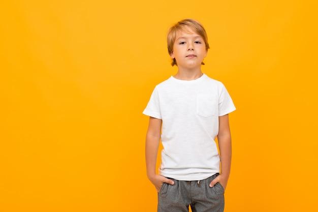 Rapaz europeu em uma camiseta branca em uma parede laranja com espaço de cópia