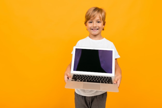 Rapaz europeu mantém a tela do laptop para a frente na parede amarela com espaço de cópia