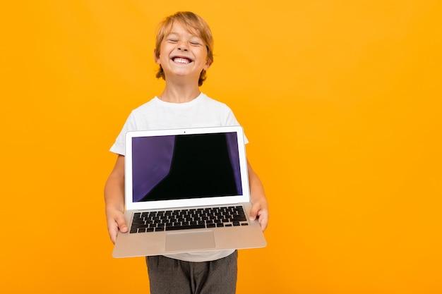 Rapaz europeu mantém a tela do laptop para a frente na parede laranja com espaço de cópia