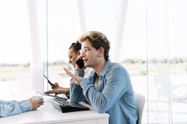 Rapaz, falando com o telefone móvel, fazendo gestos com as mãos em uma mesa de trabalho junto com outras pessoas