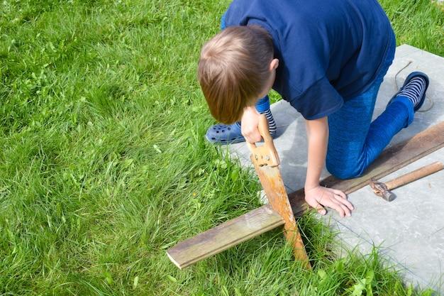 Rapaz faz trabalhos de construção. ajudante do papai. criança com uma ferramenta de construção. jovem construtor