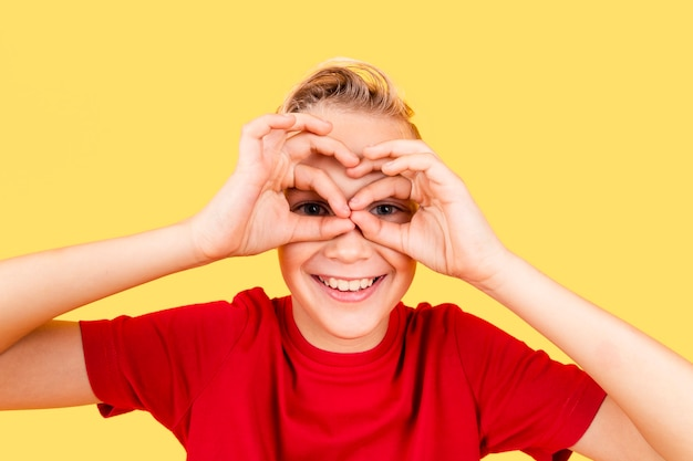 Rapaz fazendo binóculo com as mãos nos olhos